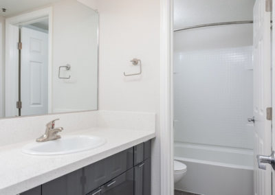 Modern white bathroom interior with sink, bathtub and mirror in place