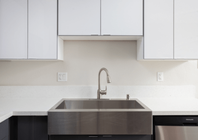 stainless steel farmhouse sink with quartz countertops, and custom cabinetry