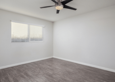Wood style flooring, ceiling fan and window with blinds open