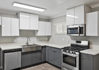 White upper cabinets with grey lower cabinets with quartz counters and stainless steel appliances