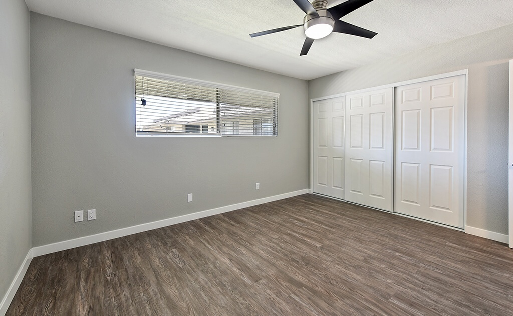 Bedroom with ceiling fan and spacious closet and window