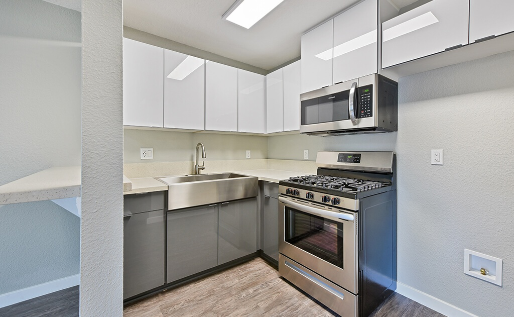 kitchen with stainless steel appliances and wood style flooring and white cabinets