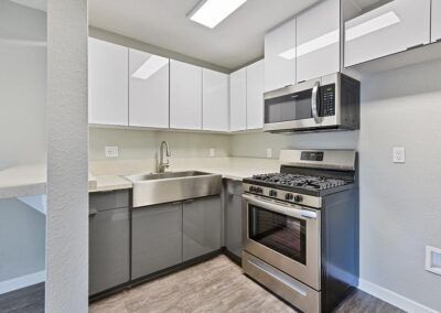 kitchen area with stainless steel appliances and clean white cabinets at angled view