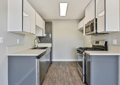 kitchen area with stainless steel appliances and clean white cabinets